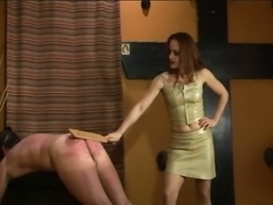 Sexy redhead mistress spanks slave's ass with different things