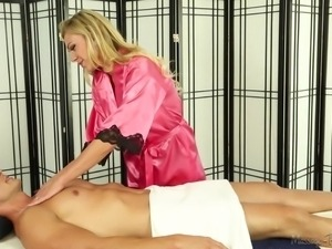 blonde gives a blowjob on the massage table