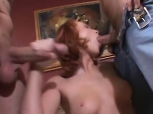 Redhead Vixen has her hands full of cock. Two studs take