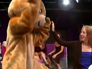 A dude is dancing for some women in his bear costume. The girls rip if off...
