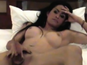 Asian tranny posing naked on bed while sucking massive dick