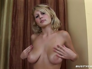 Young blonde tart plays with her tits after stripping on the bed