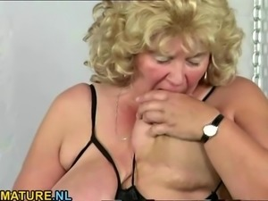 Blonde mature playing with her big boobs