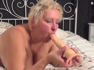 Horny grandma sucks a dildo before ramming her wet cunt