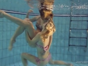Two white young sexy girls dive in the pool and undress on cam