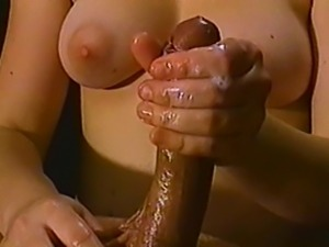 A talented brunette oils up his cock and gives him a handjob