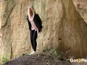 Straight blond haired cutie leans over the rock and pees right away