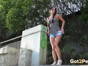 Cute brunette pulls her jeans shorts down to pee outdoors
